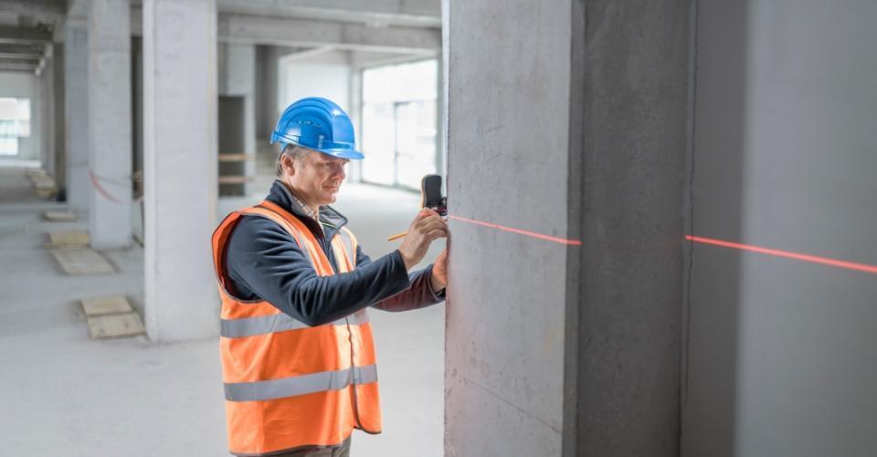 Pracownik wkamizelce ikasku wykonuje pomiar laserem